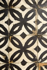 Antique floor tiles abraded backdrop in corridor.