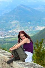 Woman sitting on a ledge.