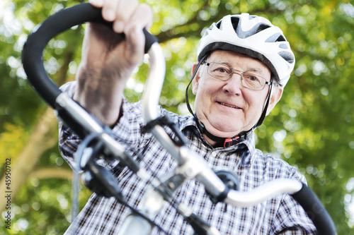 Leinwanddruck Bild seniior mit fahrrad