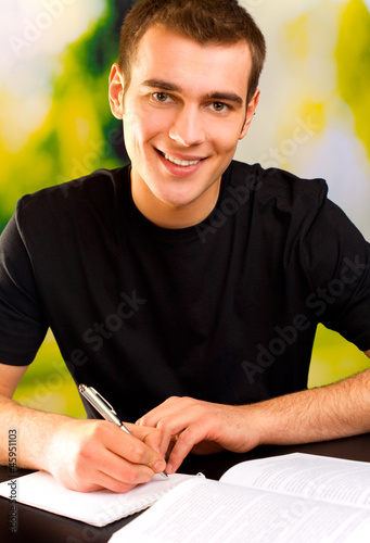 Young smiling man writing, outdoor