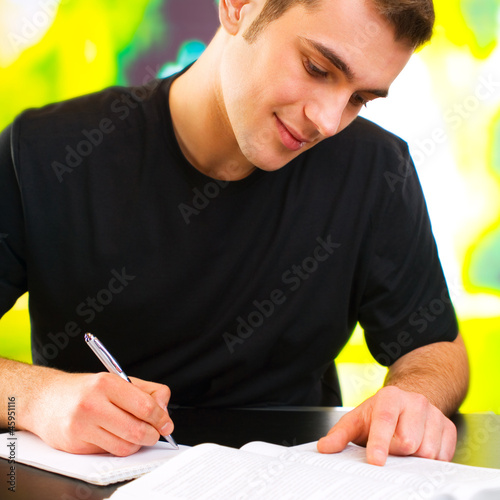 Young happy smiling man writing, outdoor