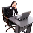 Young businesswoman sitting at desk with laptop