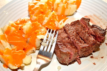 Sliced Filet Mignon with French Dressing Over a Potato