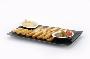 crostini di pane su piatto nero con creme