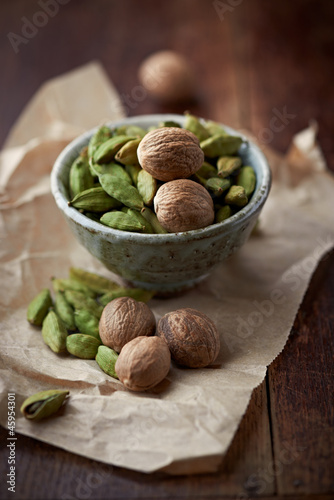 Dried cardamon pods and nutmeg in a dish