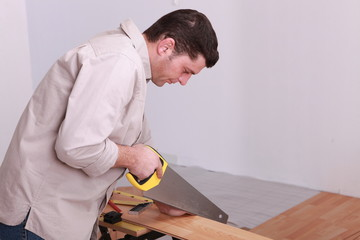 Man sawing laminate flooring