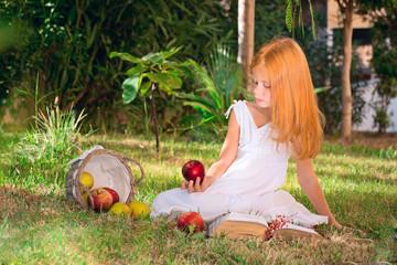 Девочка сидит на поляне с яблоками