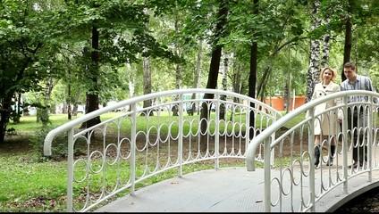Двое влюблённых идут по мостику парка
