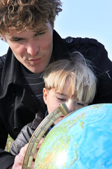 Father and son examining globe