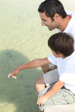 Father and son sat on jetty