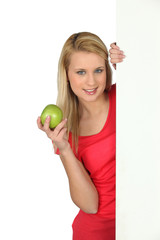 Woman behind white panel holding apple