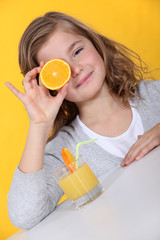 Girl covering her eye with orange slice