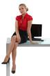 Blond businesswoman sat on desk