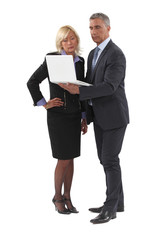 mature businessman standing with laptop and female counterpart