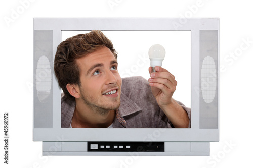 Man fitting light bulb inside television
