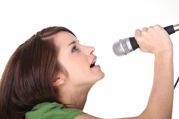 Studio shot of a young woman singing into a microphone