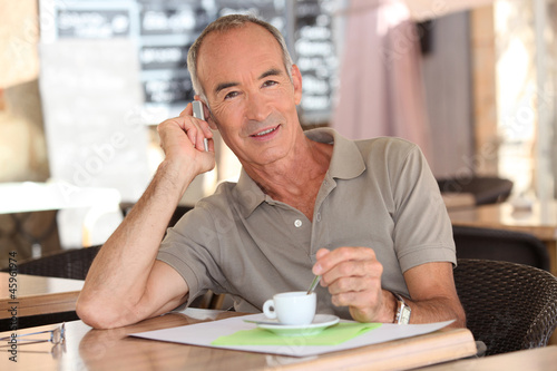 Senior having an expresso while talking on his cellphone