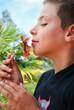 garçon sentant une fleur