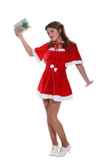 Sexy Miss Santa holding aloft a silver wrapped gift