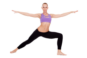 Young yoga woman doing warrior pose