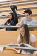Student sitting at the lecture hall with hand up