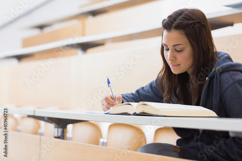 Girl reading a book and writing notes