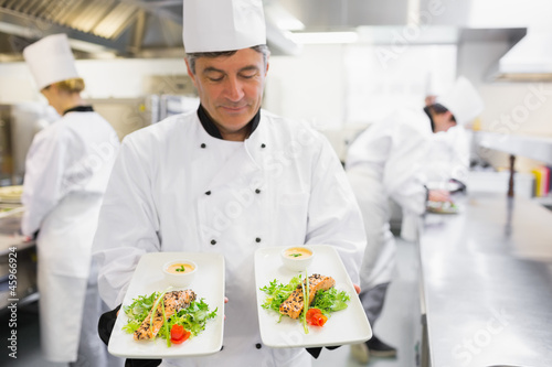 Chef admiring two salmon dishes in his hands