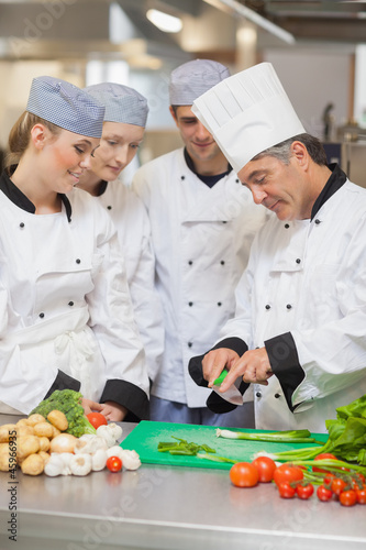 Chef teaching trainees how to cut vegetables