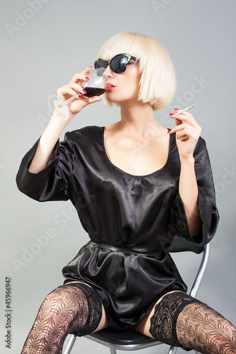 Blond girl with sunglasses holding a glass of wine