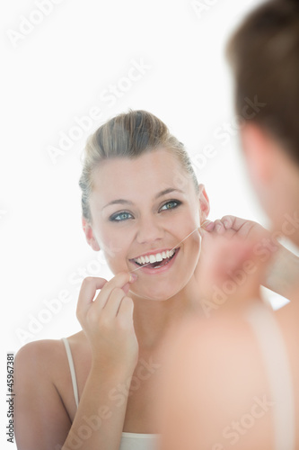 Woman using dental floss in front of mirror