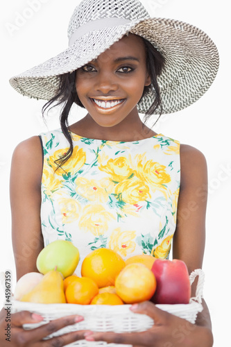 Woman standing holding a fruit basket