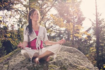 Frau bei Yoga auf einem Stein