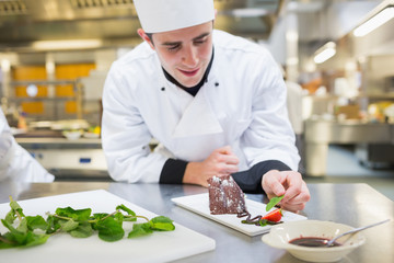 Cheerful chef putting mint with his dessert