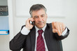 Businessman phoning and pointing