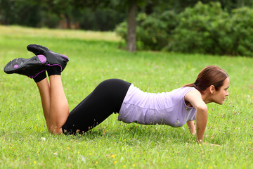 Young and cute sporty girl do her push-ups exercises in the park