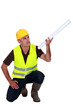 Tradesman holding up a rolled-up blueprint
