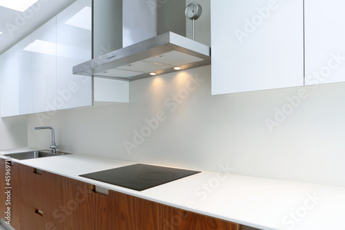 Actual modern kitchen in white and walnut wood