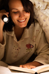Smiling Woman Reading a Book with Flashlight on Bed