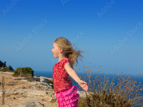 blue day with kid girl open hands to the wind