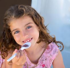 Blue eyes kid girl eating breakfast with spoon