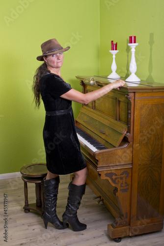 eine frau mit stiefeln steht vor einem klavier von lizenzfreies foto 45971967 auf. Black Bedroom Furniture Sets. Home Design Ideas
