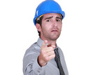 Man with a hard hat pointing at camera.