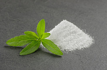Steviablätter mit Steviapulver auf einer Schieferplatte