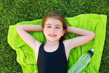 children girl relaxed lying on towel over green grass