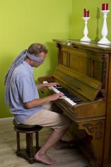 Ein Mann spielt Klavier mit verbundenen Augen