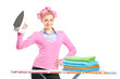A smiling woman with hair rollers holding an iron and ironing bo