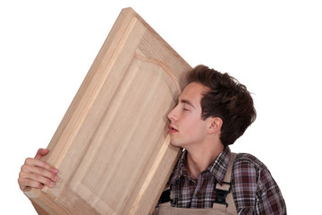 Man nuzzling a hand-crafted piece of wood