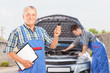 Mechanic holding a car key and another mechanic performing a che