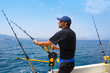 blue sea fisherman in trolling boat with downrigger