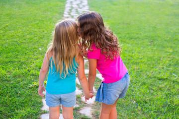 friends sister girls whispering secret in ear in garden